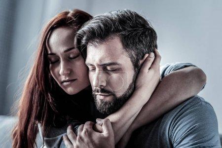 Photo pour Je t'aime tellement. rousse satisfait jeune femme étreignant son mari fermer ses yeux passer du temps ensemble . - image libre de droit