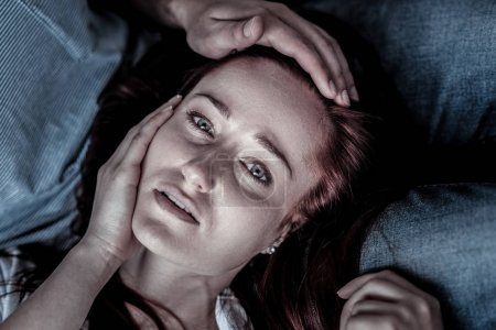 Frustrated depressed woman lying and touching her face.
