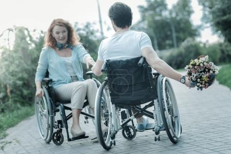 Photo for Have surprise. Silhouette of attractive woman that looking at her husband and sitting on wheelchair while having date - Royalty Free Image