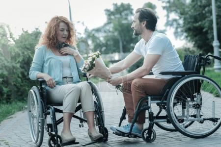 Photo for Thank you. Serious bearded man sitting in semi position and holding flowers while looking at his woman - Royalty Free Image