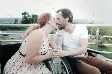 Photo for Sweet kiss. Happy bearded sitting on his wheelchair and turning head while looking at his girlfriend - Royalty Free Image