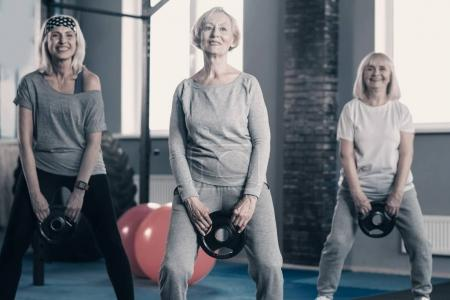 Senior ladies standing with weight discs in gym