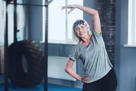 Cheerful mature lady stretching during training session