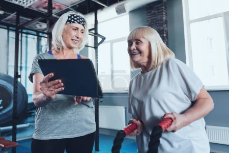 Mature lady showing her friend digital tablet at fitness club