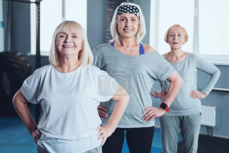 Motivated senior ladies posing with smile for camera