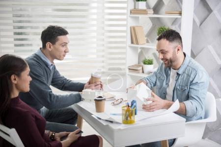 Photo pour Mes chers collègues. Beau jeune homme aux cheveux bruns souriant assis à sa table et discutant de travail avec ses collègues - image libre de droit