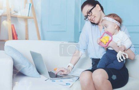 Photo pour Tant de choses à faire. Positif belle jeune femme travaillant sur l'ordinateur portable et parlant au téléphone tout en tenant son enfant - image libre de droit