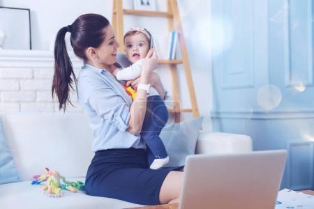 Photo pour Je t'aime tellement. Joyeuse femme heureuse positive tenant sa fille et souriant tout en la regardant - image libre de droit