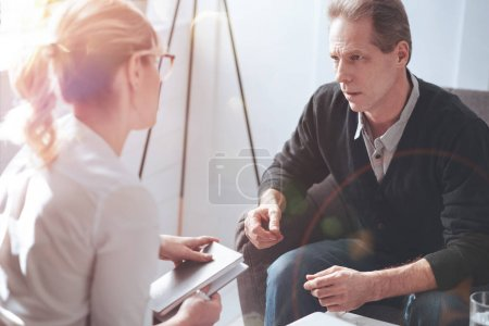 Photo for Psychological session. Sad moody unhappy man sitting on the sofa and looking at his therapist while having a psychological session with her - Royalty Free Image