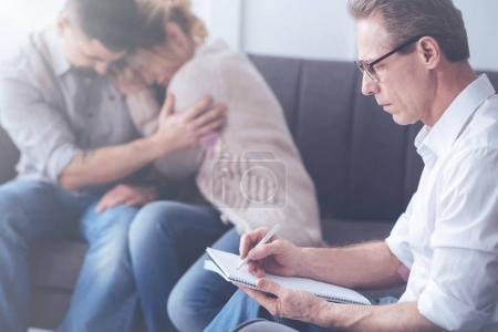 Serious male psychologist working with a married couple