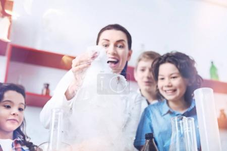 Excited female teacher conducting practical chemistry lesson