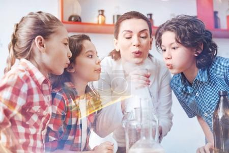 Photo for Work in team. Female chemistry teacher conducting a practical lesson with her pupils and involving them in the process of performing a chemical experiment. - Royalty Free Image