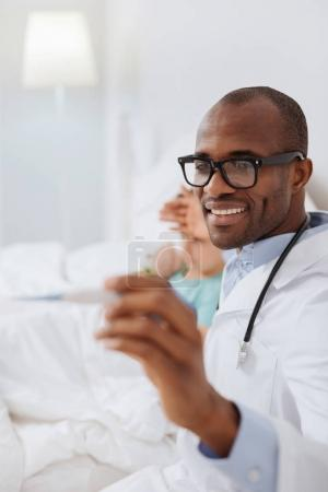 Jolly male doctor monitoring boys temperature