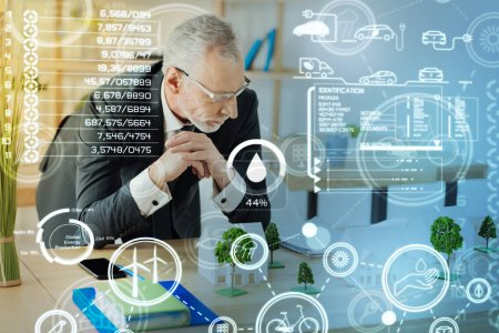 Photo for Looking concentrated. Calm clever mature engineer attentively looking at the miniature houses and trees on his table while working at the new interesting project in his light comfortable office - Royalty Free Image