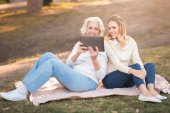 Concentrated woman enjoying picnic with retired mother in the park