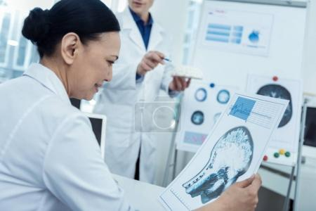 Professional scientist holding brain image