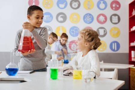 Photo for Important discussion. Charming teenage boy holding a big flask with a red liquid and talking with his team member during chemistry class - Royalty Free Image
