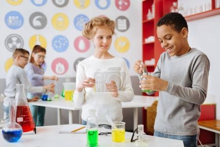 Photo for Interesting experiment. Joyful teenage boy adding green chemical to the flask with a pipette and smiling while his experiment partner looking at him with curiosity - Royalty Free Image