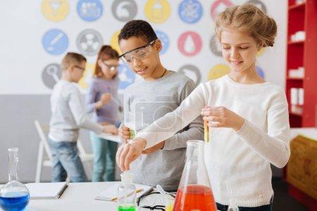 Foto de Interesante química. Encantadora adolescente sosteniendo un tubo de ensayo con una sustancia química y tomando algunos mililitros de otro de un frasco mientras realiza un experimento químico con su compañero de clase - Imagen libre de derechos