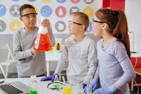 Photo for Exciting experiment. Charming teenage boy holding a big flask and demonstrating the chemical reaction to his classmates while they all wearing safety goggles - Royalty Free Image