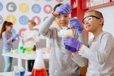 Photo for Have a look. Joyful teenage boy showing a flask with fuming liquid in it to his friend while the boy conducting his own experiment during a chemistry class - Royalty Free Image