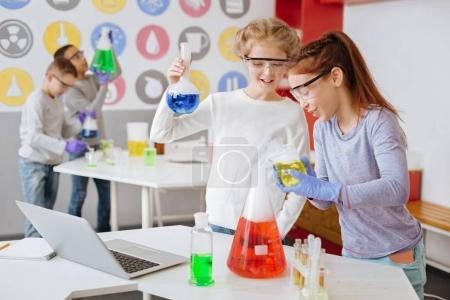 Photo for Correct reaction. Charming teenage schoolgirls holding chemical flasks and checking the correctness of chemical reaction taking place in them - Royalty Free Image