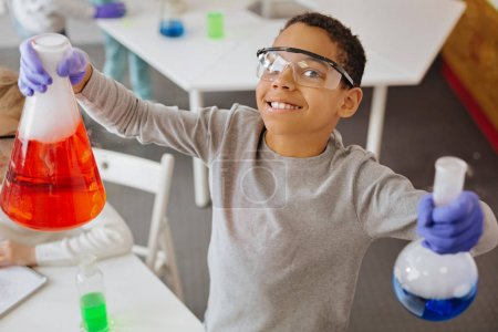 Photo for Enthusiastic experimenter. The top view of a pleasant upbeat teenage boy in safety glasses smiling at the camera while holding two chemical flasks with red and blue liquids - Royalty Free Image