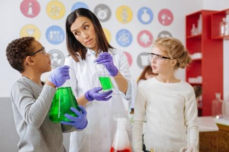 Photo pour Une aide importante. Charmante jeune enseignante qui donne un agent chimique à son élève alors qu'il tient une fiole avec une substance et lui demande conseil - image libre de droit