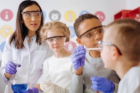 Foto de Ten cuidado. Profesora de química agradable mirando a sus estudiantes con una expresión preocupada mientras mezclan productos químicos de una manera incorrecta - Imagen libre de derechos