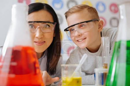 Photo for Favorite science. The close up of an upbeat teenage student and his young chemistry teacher watching the chemicals reacting in the flasks during the class in the lab - Royalty Free Image