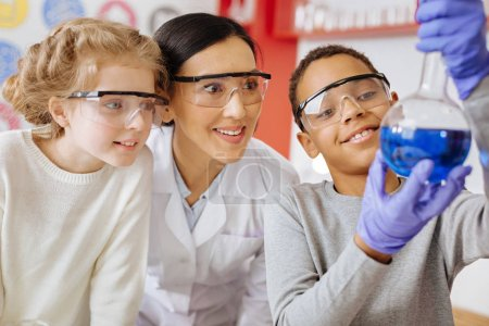 Photo for Proud with result. Pleasant teenage male student lifting up a flask with a chemical substance and showing it to his teacher and classmate proudly while they looking with surprise - Royalty Free Image