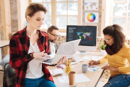 Photo pour Mon cher travail. Belle femme blonde concentrée qui travaille sur son ordinateur portable alors qu'elle est assise sur la table et ses collègues qui travaillent en arrière-plan - image libre de droit