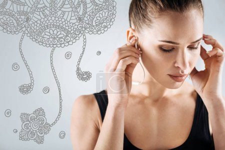 Beautiful sportswoman closing her eyes while listening to music