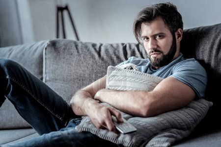 Photo for All alone. Unhappy cheerless bored man holding a remote control and hugging a sofa cushion while suffering from loneliness - Royalty Free Image