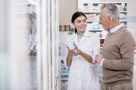 Positive female pharmacist helping senior man