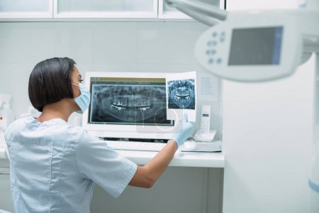 Female dentist holding an image
