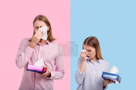 Upset young couple wiping tears with tissues