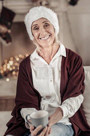 Photo pour Un amateur de thé. Femme âgée souriante assise dans son salon et portant un chapeau de Père Noël tout en célébrant Noël - image libre de droit