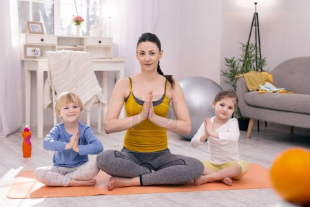 Content mother and her children doing yoga