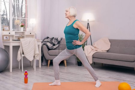 Pleasant senior woman doing lunges in the morning