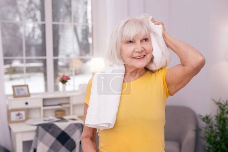 Charming elderly woman towel-drying her hair after workout