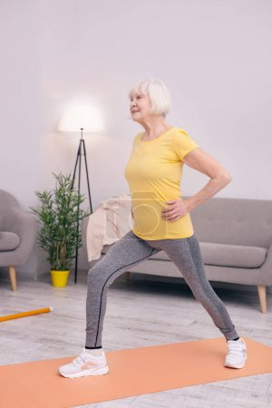 Pleasant elderly woman doing lunges at home