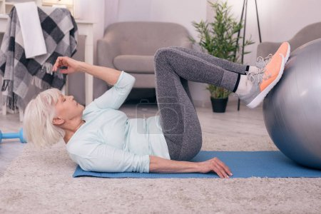 Athletic senior woman working out her abs