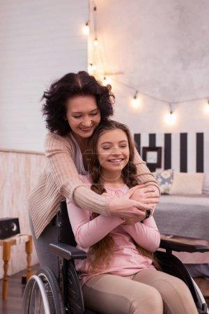 Jovial woman embracing disabled girl