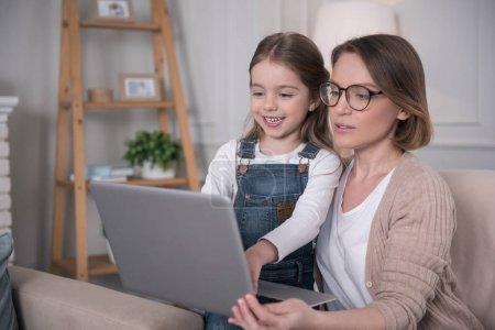 Photo pour Travailler ensemble. Aimer alerte mère assis avec sa fille et de travailler sur l'ordinateur portable - image libre de droit