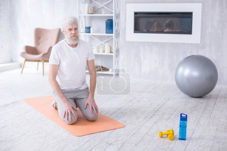 White-haired senior man kneeling on yoga mat
