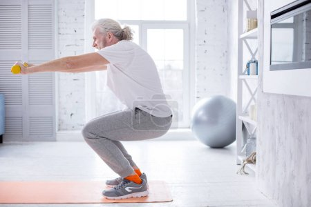 Photo for Energetic exercise. Fit elderly man standing on the yoga mat at home and doing squats while holding a pair of dumbbells - Royalty Free Image