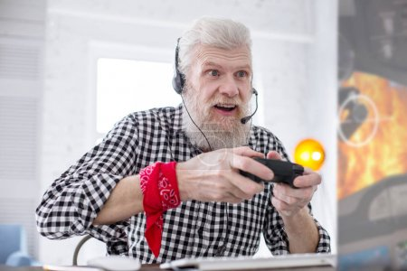 White-haired senior man being excited about playing video game