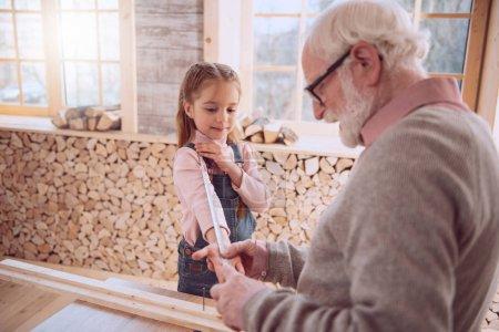 Photo pour C'est pour combien de temps ? Positif fille mignonne mesure sa main tout en étant avec son grand-père - image libre de droit