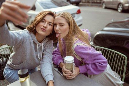 Foto de Atractiva rubia mostrando su lengua mientras hace el amor con su amiga. - Imagen libre de derechos